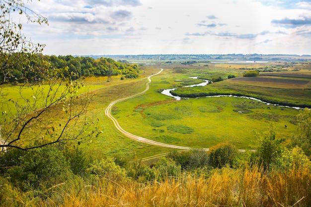 Campo de outono da colina. estrada na natureza. bela paisagem com um rio.