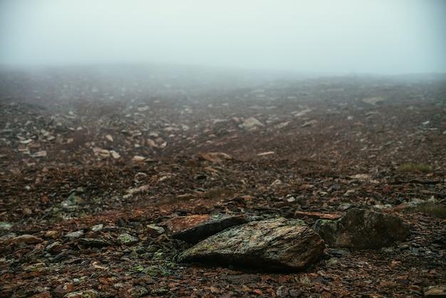 Campo de pedra em denso nevoeiro nas terras altas. deserto de pedra vazio em espesso nevoeiro. visibilidade zero nas montanhas. fundo de natureza minimalista. paisagem de montanha nebulosa atmosférica escura. líquenes em pedras afiadas.