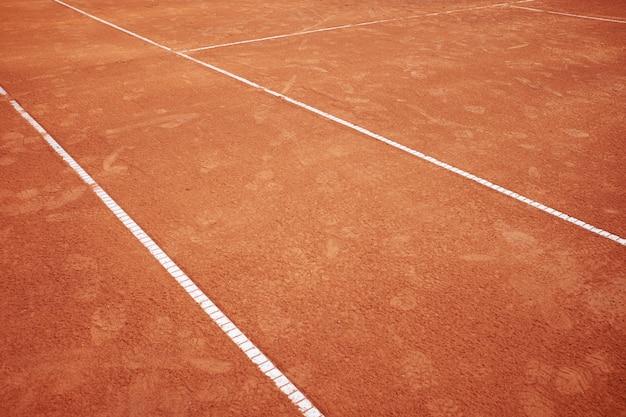 Campo de tênis de areia vermelha com fundo de linhas brancas