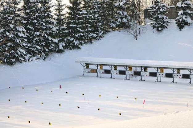 Campo de tiro coberto de neve para biatlo em um fundo de árvores.