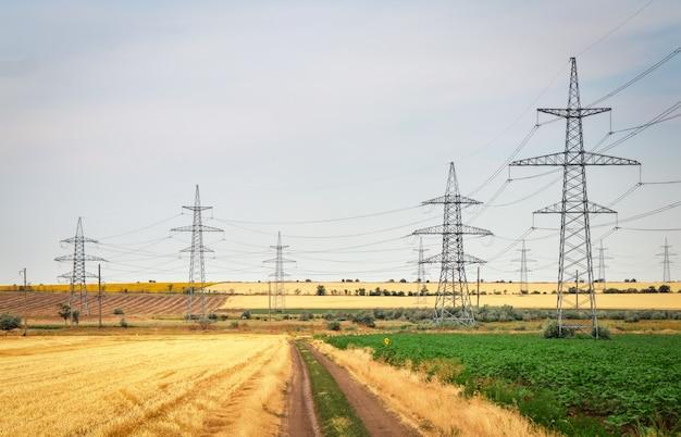 Campo de trigo dourado e céu azul. torre de silhueta de pilão de transmissão elétrica de alta tensão.