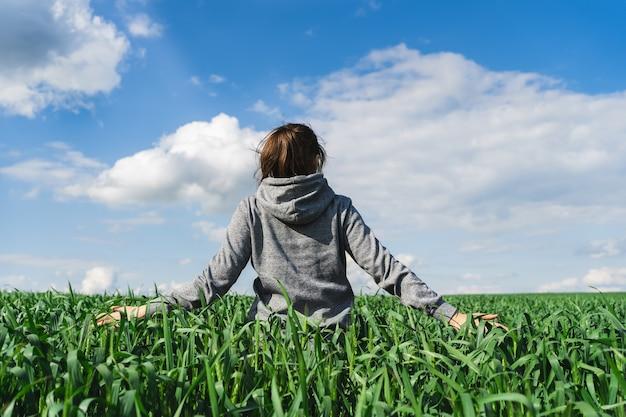 Campo de trigo verde jovem. mulher em um campo tocando espigas de trigo. conceito de colheita rica. fazendeiro ou agrônomo verifica a colheita.