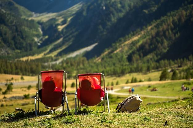 Campo gramado com duas pessoas deitadas em cadeiras apreciando a vista