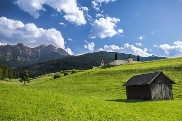 Campo gramado com uma casa de madeira e uma montanha arborizada à distância