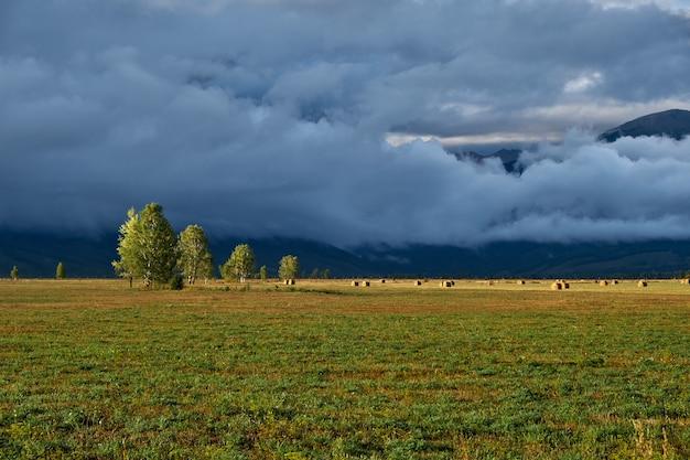 Campo, montanhas e nuvens. noite paisagem depois da chuva.