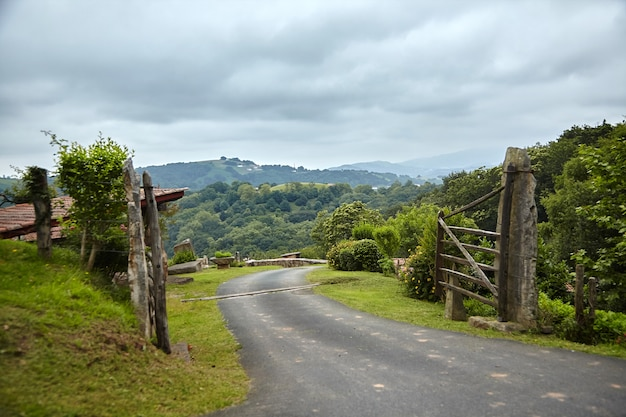 Campo na frança no sopé das montanhas cerca de madeira com portão e estrada rural