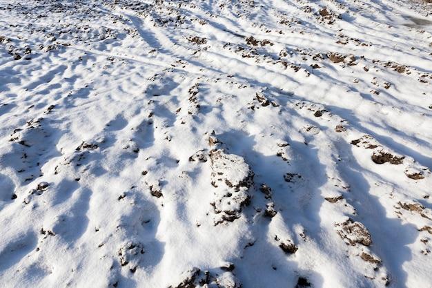 Campo no qual existem vestígios e rastros de automóveis. no inverno do ano, o solo fica coberto de neve branca após uma nevasca. close up tirado
