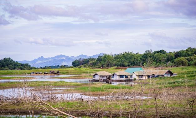 Campo perto do lago e montanha com céu nublado