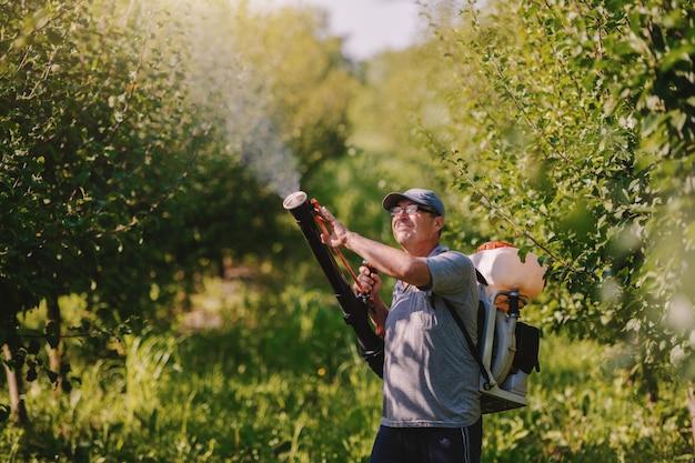 Camponês maduro caucasiano em roupas de trabalho, chapéu e com a moderna máquina de pulverização de pesticidas nas costas pulverizando insetos no pomar.