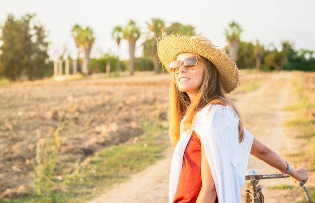 Camponesa elegante com chapéu de palha na hora do spingtime com bicicleta caminhando pelo campo sorrindo feliz