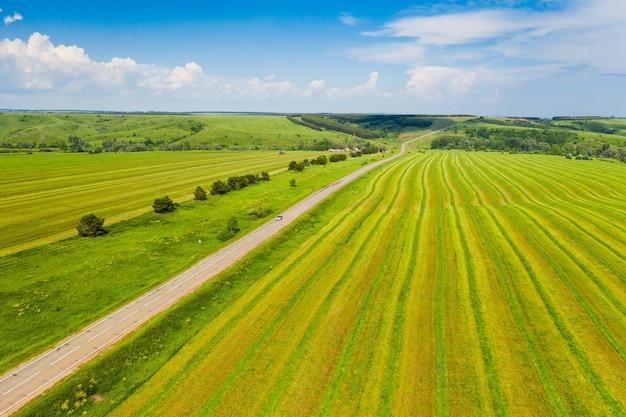 Campos e uma estrada contra um céu azul tomado por um quadrocopter
