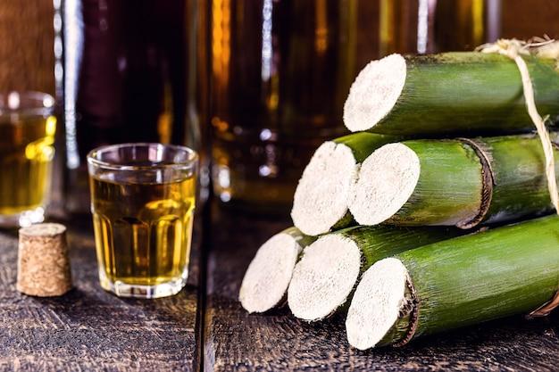 Cana-de-açúcar utilizada em bebidas destiladas, fundo de barril e copo com bebida alcoólica