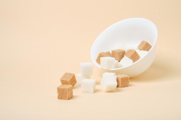 Cana marrom e cubos de açúcar branco em uma tigela branca no espaço bege da superfície da cópia