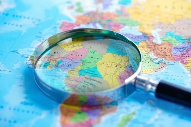 Canadá: lupa com mapa de luva do mundo.