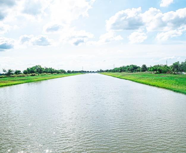 Canais de transporte e distribuição de água. um canal de irrigação com um caminho percorrendo ao longo dele entre campos verdes e céu azul. bela paisagem em bang len, nakhon pathom, tailândia