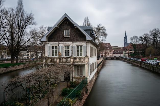Canal cercado por edifícios e vegetação sob um céu nublado em estrasburgo, na frança