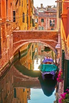 Canal com pequena ponte e gôndola ancorada em veneza no início da noite, itália