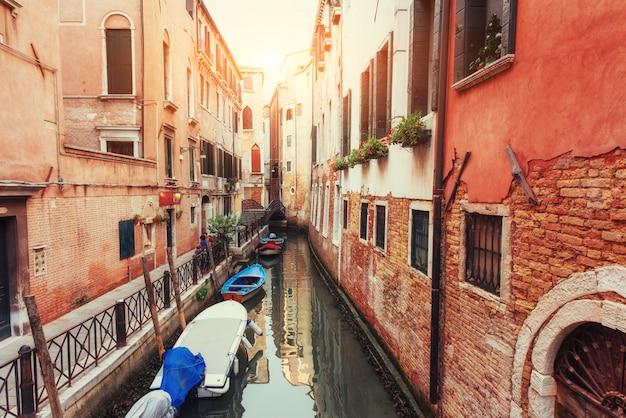 Canal de água verde com gôndolas e fachadas coloridas