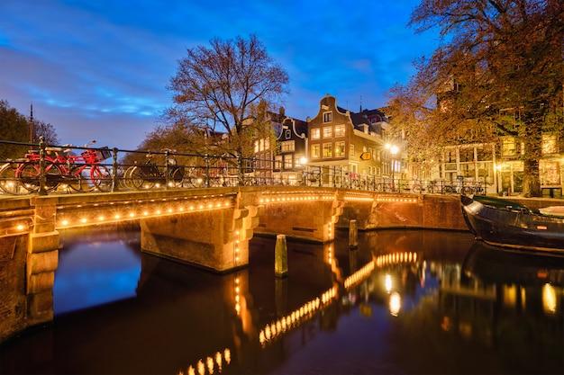 Canal de amesterdão, ponte e casas medievais à noite