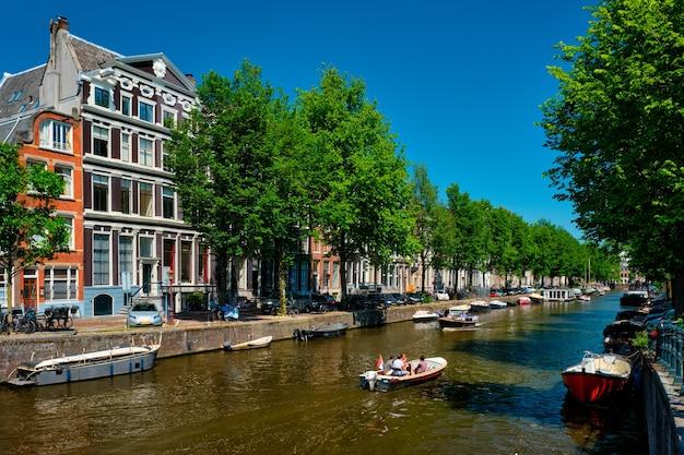 Canal de amsterdã com barco turístico e casas antigas