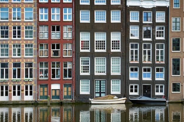 Canal de amsterdã damrak com casas, holanda