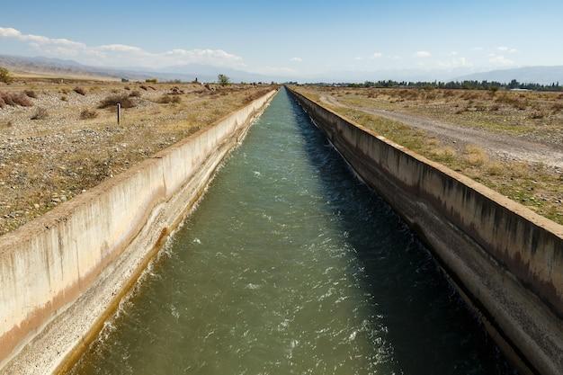 Canal de irrigação província de chuy. água fluindo em um canal de irrigação no quirguistão.