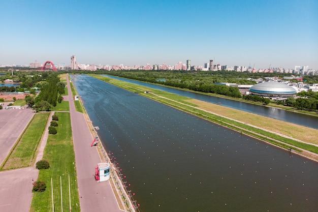 Canal de remo iluminado pela luz do sol. vista panorâmica. filmagem de cima, filmagem aérea. canal de remo olímpico em moscou.