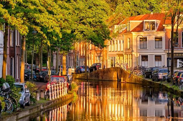 Canal delt com casas antigas e carros estacionados ao pôr do sol