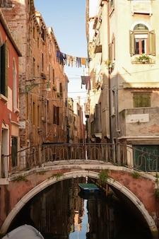 Canal em veneza italiana entre edifícios antigos com barcos nele. e uma ponte pedonal nesta ponte.
