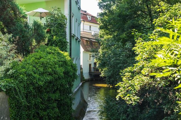 Canal estreito, rio entre casas antigas na cidade velha de praga, república checa, europa. casas europeias em vegetação, com varandas e terraços