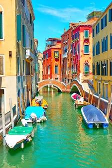 Canal pitoresco com pequena ponte e barcos atracados em veneza, itália