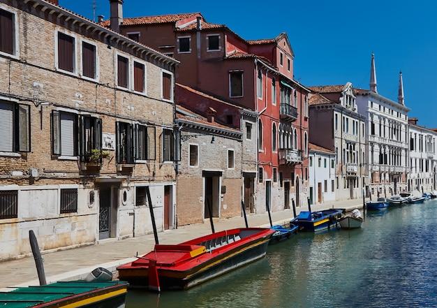 Canal tradicional com barcos em veneza, itália. verão.