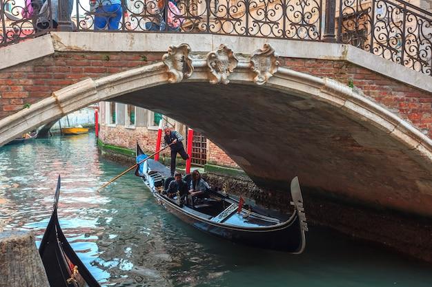 Canal veneziano com gôndolas e casas históricas.