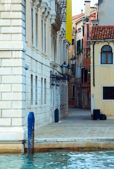 Canal veneziano de verão e vista estreita da rua