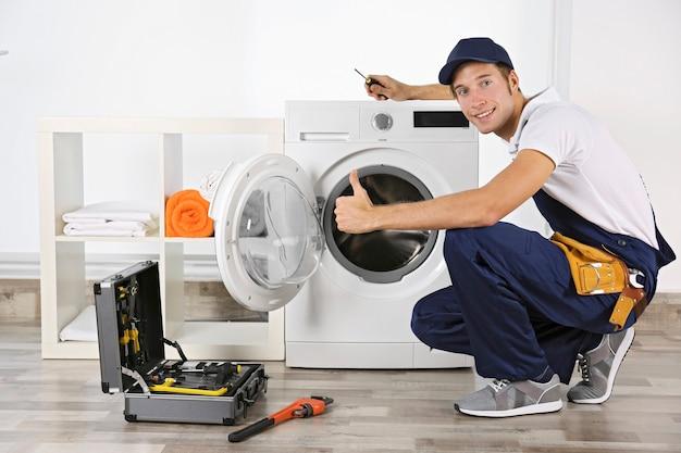 Canalizador consertando máquina de lavar