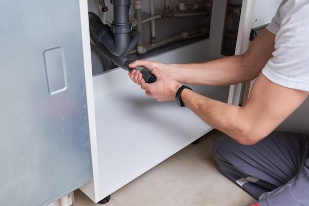 Canalizador masculino consertando cano na cozinha