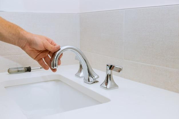 Canalizador que fixa a torneira de instalação de uma pia no trabalho no banheiro