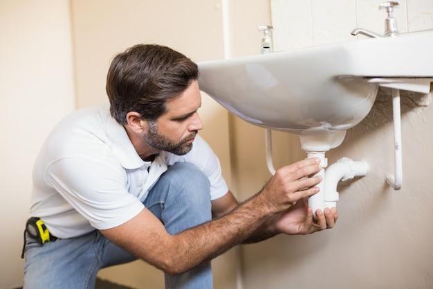 Canalizador que repara a pia em uma casa de banho