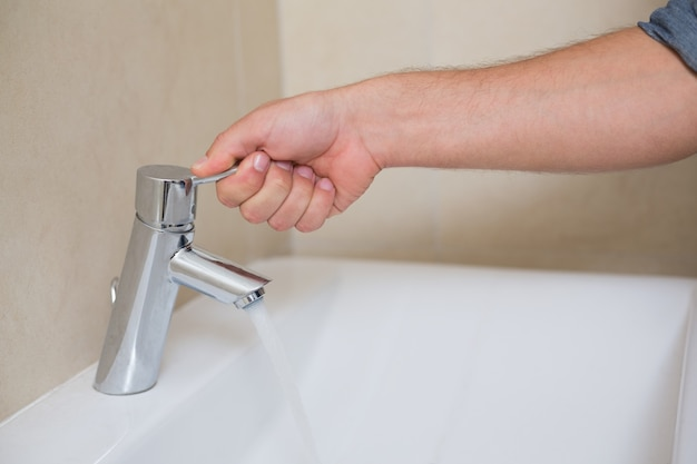 Canalizadores abrem uma torneira de água no banheiro