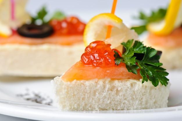 Canape com caviar vermelho e salmão defumado, servido no prato