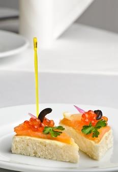 Canape com kaviar vermelho e salmão defumado, servido no prato