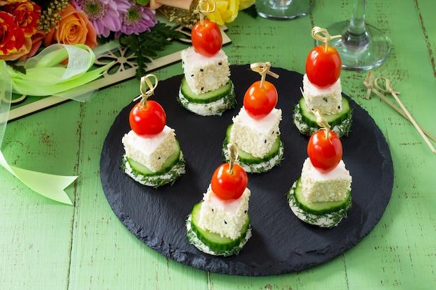 Canapé com pão branco, pepino, queijo feta e tomate cereja em uma mesa festiva. dia dos namorados ou casamento.