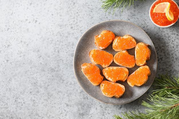 Canapé de aperitivo russo com caviar vermelho sobre fundo branco para o natal.