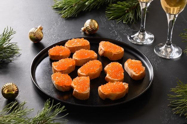 Canapé de aperitivo russo com caviar vermelho sobre fundo preto para o natal.