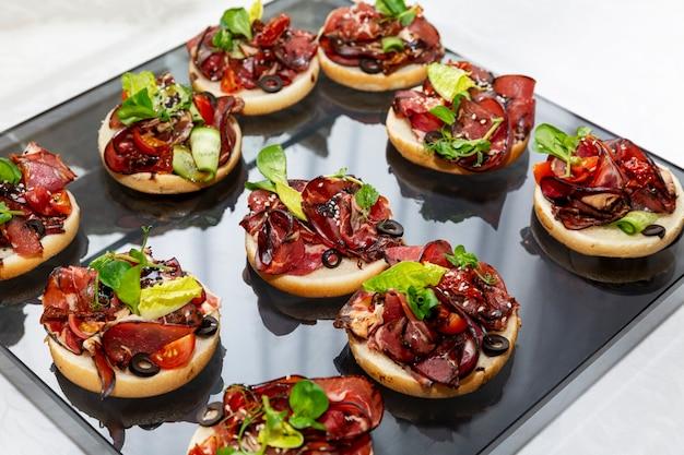 Canapés apetitosos com sanduíches de carne. catering para reuniões de negócios, eventos e celebrações.