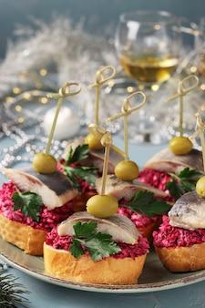 Canapés com arenque salgado, azeitonas e beterrabas em croutons de pão branco em um prato sobre uma mesa azul clara. formato vertical. fechar-se