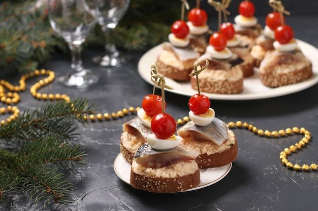 Canapés com arenque salgado, queijo, ovos de codorna e tomate cereja em pão de centeio