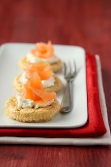 Canapés com biscoitos de farelo de aveia, salmão defumado e cream cheese
