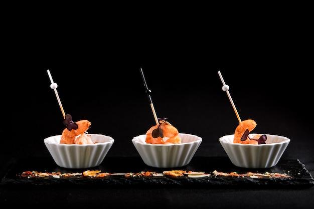 Canapés com camarão tigre no espeto. o conceito de restauração de alimentos.