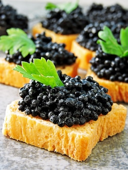 Canapés com caviar preto.
